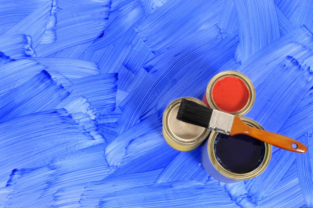 latas de tintas e pincel com fundo azul de tinta