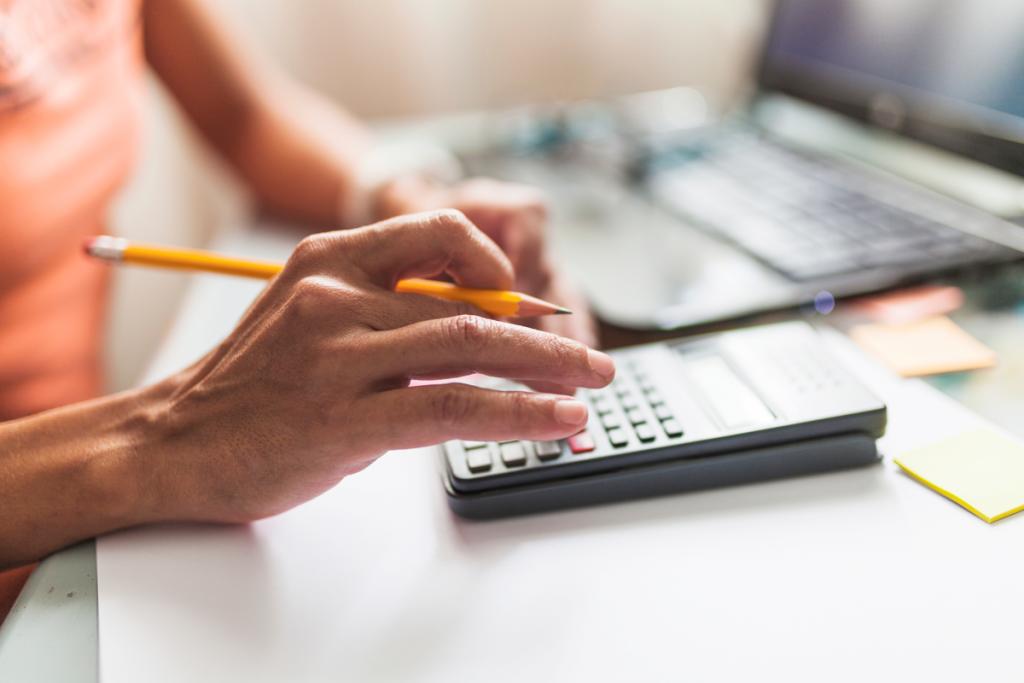 mulher usando calculadora para calcular o iptu